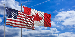 American and Canadian flags against a blue sky background